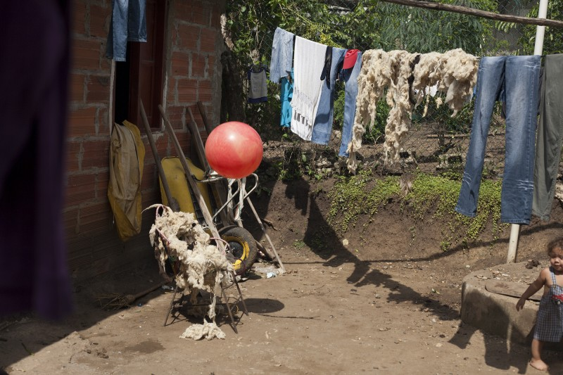 Wool dries on the clothesline in Gavelys' back yard. She weaves the traditional Indigenous bags and sells them in El Centro. A part of her story was told in the women's play at FUNSAREP; the episode whrein the FARC returned to her farm and slaughtered the livestock as a threat.