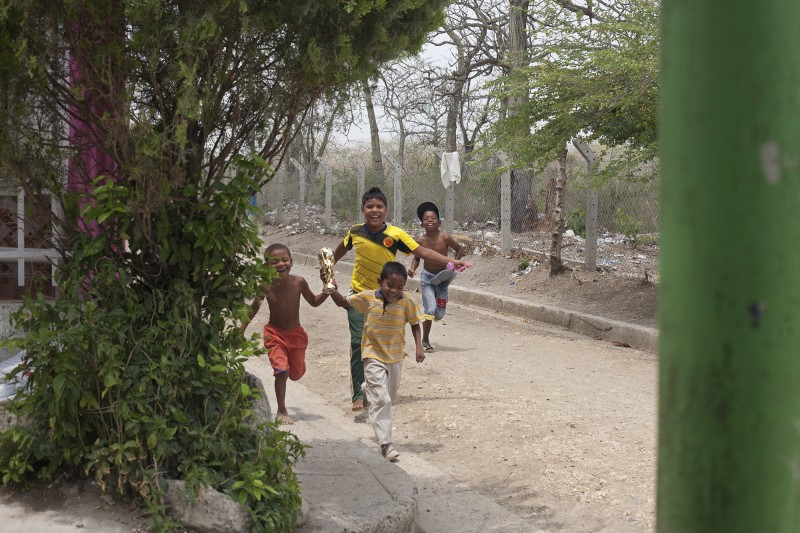 Kids run with a newly minted trophy near Yuris' house in San Jose de los Campanos, a sprawling barrio on the periphery of Cartagena. Although these communities are tight, the incidence of crime remains high because of the very real need for food, shelter, money.
